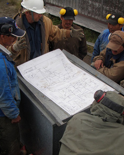 photo of men standing around structural plans of a wind turbine
