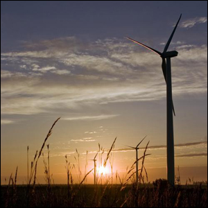 A photo of a sunset, large wind turbines, and wheat.