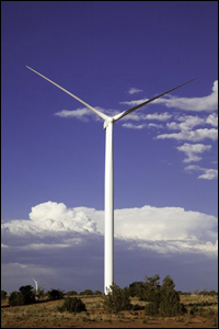 A photo of a large wind turbine surrounded by desert landscape.