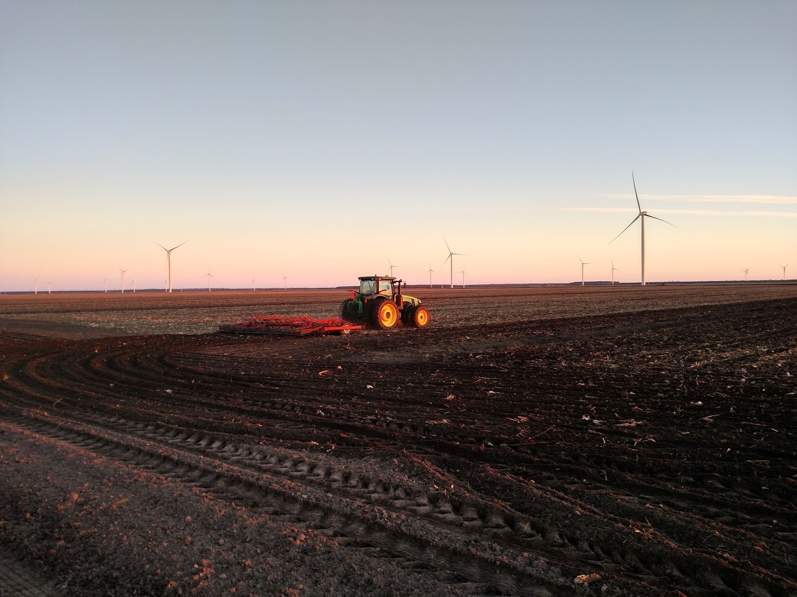 Farm equipment working in a field in front of a backdrop of wind turbines.